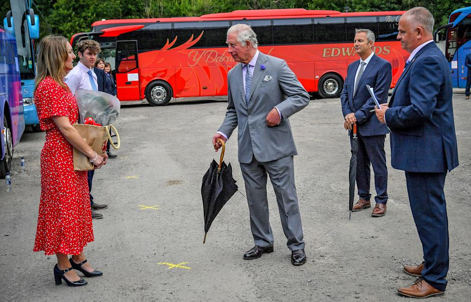Britain's Prince Charles, Prince of Wales (C) reacts during his visit to family run travel and holiday business, Edwards Coaches, in Abercynon, near Mountain Ash, south Wales, on July 13, 2020. - The company has been impacted by the COVID-19 pandemic, but is now beginning to restart some of their operations. (Photo by Ben Birchall / POOL / AFP) (Photo by BEN BIRCHALL/POOL/AFP via Getty Images)