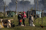 A family with their pet dog stands with their belongings after their shack home was destroyed by police carrying out the eviction of a squatters camp in Guernica, Buenos Aires province, Argentina, Thursday, Oct. 29, 2020. A court ordered the eviction of families who are squatting here since July, but the families say they have nowhere to go amid the COVID-19 pandemic. (AP Photo/Natacha Pisarenko)
