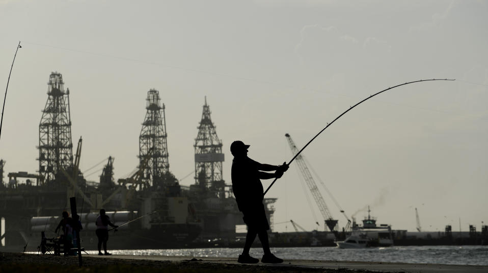 A man fishes near docked oil drilling platforms, Friday, May 8, 2020, in Port Aransas, Texas. Texas' stay-at-home orders due to the COVID-19 pandemic have expired and Texas Gov. Greg Abbott has eased restrictions on many businesses, churches, state parks and beaches. (AP Photo/Eric Gay)