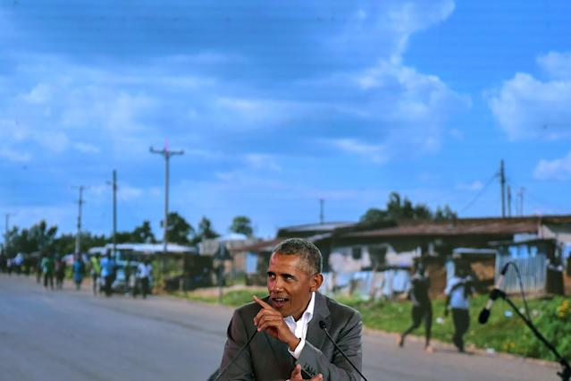 <p>Former US President, Barack Obama gestures as he makes an address on July 16, 2018 in front of a projected backdrop showing a view of his father's home village, the hamlet of Nyang'oma in Kogelo, during the opening of the Sauti Kuu Resource Centre founded by his half-sister, at Kogelo in Siaya county, western Kenya. – Obama is in the east african nation for the first time since he left the US presidency and met with President Uhuru Kenyatta and opposition leader Raila Odinga in Nairobi. (Photo: Tony Karumba/AFP/Getty Images) </p>