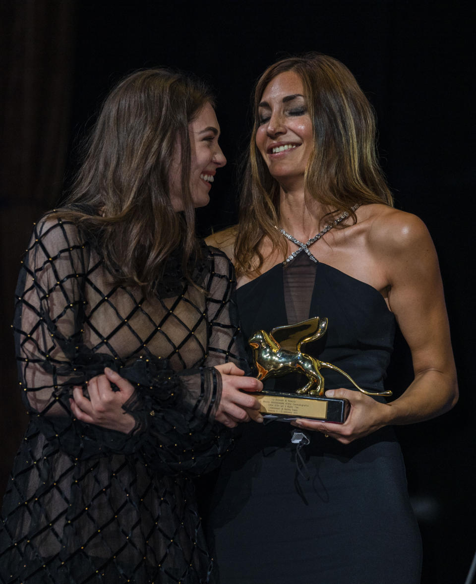 FILE - In this Sept, 11, 2021 file photo Anamaria Vartolomei, left, congratulates director Audrey Diwan as she holds the Golden Lion award for 'Happening' onstage at the closing ceremony during the 78th edition of the Venice Film Festival in Venice, Italy. (AP Photo/Domenico Stinellis, File)