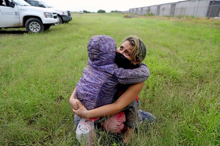 LA JOYA, TEXAS - JUNE 02: Mileydi (cq) Barrela, 26, of Tegucigalpa, Honduras, and daughter Zoe Barrela, eight, who crossed the U.S.-Mexico border illegally, wait to be loaded on a bus to be processed by U.S. Border Patrol, Rio Grande Valley Sector, on Wednesday, June 2, 2021 in La Joya, Texas. There have been 221,115 migrants caught who have crossed the border illegally through April 2021 in the Rio Grande Valley Sector. Increased numbers of adult migrants crossing the border illegally, avoiding Border Patrol along the Rio Grande. (Gary Coronado / Los Angeles Times)