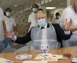 Britain's Prime Minister Boris Johnson takes part in an activity, during a visit to Westport Care Home in Stepney Green, east London, Tuesday, Sept. 7, 2021, ahead of unveiling his long-awaited plan to fix the broken social care system. (Paul Edwards/Pool Photo via AP)
