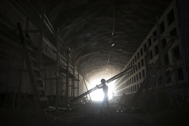 In this Sunday, Aug. 18, 2019 photo, a worker carries boards at the construction site of a massive underground cemetery in Jerusalem. Under a mountain on the outskirts of Jerusalem, workers are completing three years of labor on a massive subterranean necropolis comprised of a mile (1.5 kilometers) of tunnels with sepulchers for interring the dead. (AP Photo/Oded Balilty)