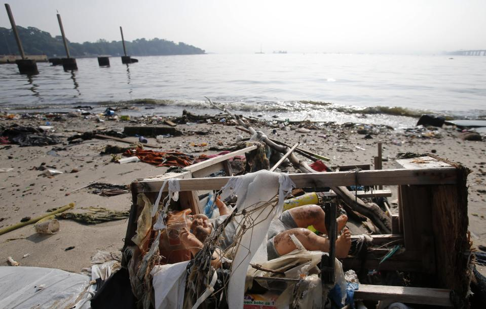 A toy doll is seen on Fundao beach in the Guanabara Bay in Rio de Janeiro March 13, 2014. According to the local media, the city of Rio de Janeiro continues to face criticism locally and abroad that the bodies of water it plans to use for competition in the 2016 Olympic Games are too polluted to host events. Untreated sewage and trash frequently find their way into the Atlantic waters of Copacabana Beach and Guanabara Bay - both future sites to events such as marathon swimming, sailing and triathlon events. REUTERS/Sergio Moraes (BRAZIL - Tags: ENVIRONMENT SPORT OLYMPICS)