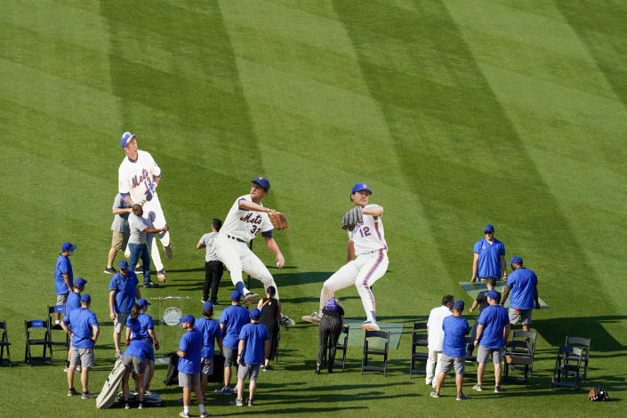 A Citi Field crew sets up giant cardboard cutouts of pitcher Ron Darling, right, pitcher Jon Matlack, center, and infielder Edgardo Alfonzo ahead of a New York Mets Hall of Fame ceremony, Saturday, July 31, 2021, in New York. (AP Photo/Mary Altaffer)