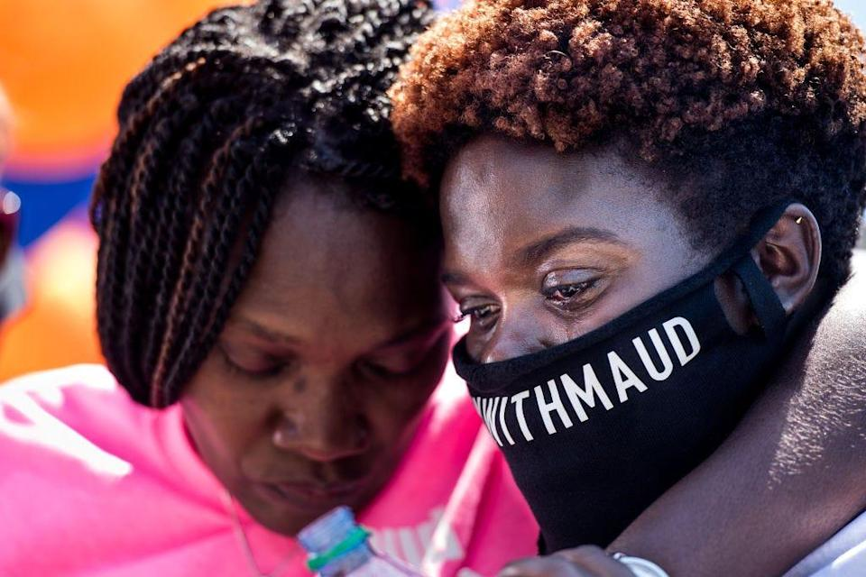 Jasmine Arbery, sister of Ahmaud Arbery, right, and Wanda Cooper-Jones, Ahmaud's mother, comfort one another while people gather to honor Ahmaud at Sidney Lanier Park on May 9, 2020, in Brunswick, Ga. Ahmaud Arbery was shot and killed while jogging in the nearby Satilla Shores neighborhood on Feb. 23, 2020.