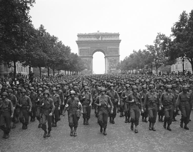 FILE - In this Aug. 29, 1944 file photo, U.S. soldiers of Pennsylvania's 28th Infantry Division march along the Champs Elysees, the Arc de Triomphe in the background, four days after the liberation of Paris, France. The fighting for the liberation of Paris took place from August 19 to August 25, 1944. (AP Photo/Peter J. Carroll, File)