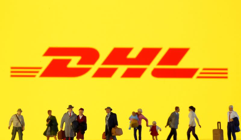 FILE PHOTO: Small toy figures are seen in front of diplayed DHL logo