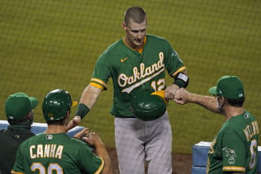 Oakland Athletics' Sean Murphy, center, returns to the dugout after scoring on a wild pitch by Los Angeles Dodgers' Dustin May during the third inning of a baseball game Tuesday, Sept. 22, 2020, in Los Angeles. (AP Photo/Ashley Landis)
