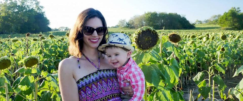 Lawrence, Kansas / United States - September 26 2015: Mom in pink printed sundress holding adorable chubby cheeked happy toddler boy in Kansas sunflower field.