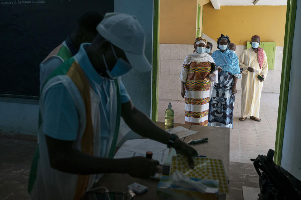 People wait in line to vote in presidential election in Abidjan, Ivory Coast, Saturday, Oct. 31, 2020. Tens of thousands of security forces deployed across Ivory Coast on Saturday as the leading opposition parties boycotted the election, calling President Alassane Ouattara's bid for a third term illegal. (AP Photo/Leo Correa)