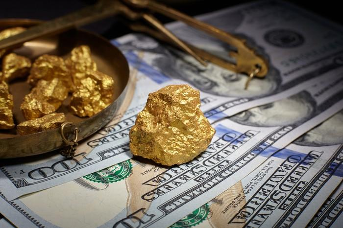 Gold nuggets on top of cash.