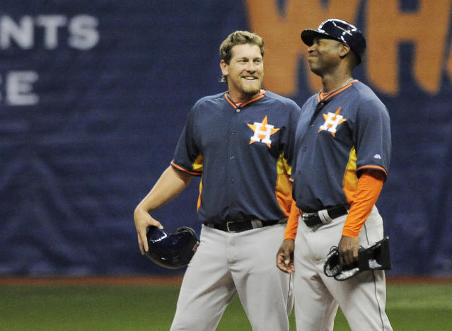 Houston Astros' Jonathan Meyer, left, jokes with first base coach Tarrik Brock during a spring exhibition baseball game against the Texas Rangers on Friday, March 28, 2014, in San Antonio. Houston won 6-5. (AP Photo/Darren Abate)