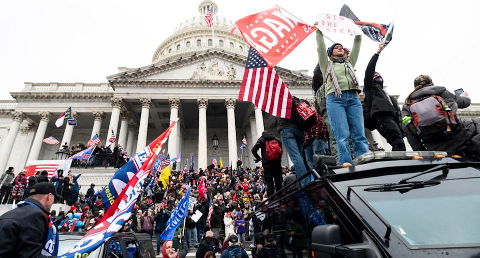 Trump supporters stand on the US Capitol Police armoured vehicle as others take over the steps of the Capitol. Source: Getty