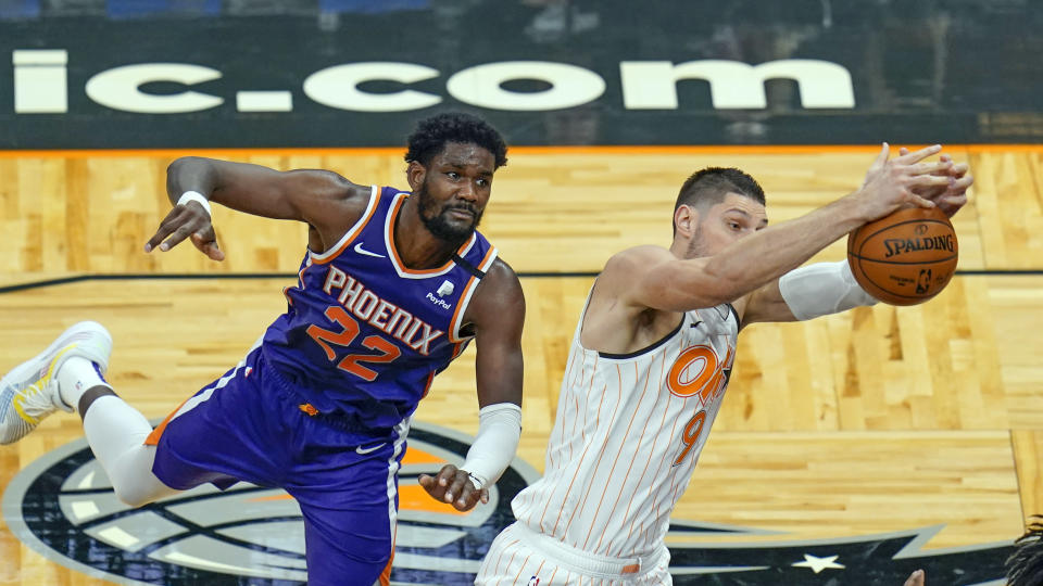 Orlando Magic center Nikola Vucevic, right, grabs a pass that was over the head of Phoenix Suns center Deandre Ayton (22) during the second half of an NBA basketball game, Wednesday, March 24, 2021, in Orlando, Fla. (AP Photo/John Raoux)