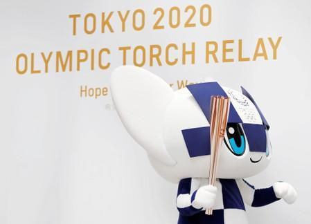 FILE PHOTO: Tokyo 2020 Olympic Games mascot Miraitowa holds the torch of the Tokyo 2020 Olympic Games during an event to mark the 300-day milestone to the start of the torch relay, in Tokyo