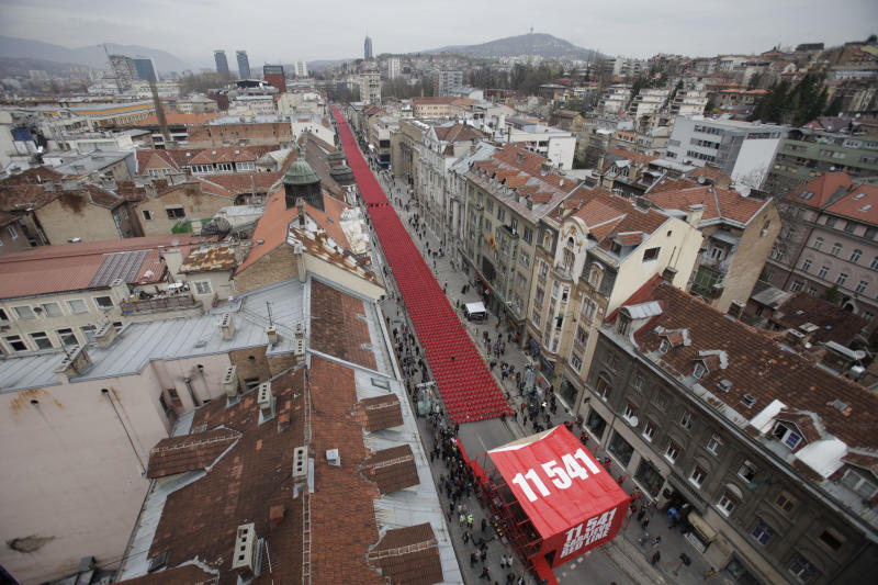 Red chairs are displayed along a main street in Sarajevo as the city marks the 20th anniversary of the start of the Bosnian war on Friday, April 6, 2012. City officials have lined up 11,541 red chairs arranged in 825 rows along the main street that now looks like a red river representing the 11,541 Sarajevans who were killed during the siege.(AP Photo/Amel Emric)