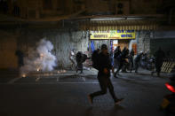 In this Thursday, April 22, 2021 file photo, Palestinians run as a stun grenades are fired by Israeli police during clashes at Damascus Gate just outside Jerusalem's Old City, Thursday, April 22, 2021. A year of relative calm between Israel and the Palestinians has come to an abrupt halt in recent days with the eruption of nightly clashes between Arab youths and Israeli police in east Jerusalem and a heavy barrage of rocket fire launched from the Hamas-ruled Gaza Strip. (AP Photo/Mahmoud Illean, File)
