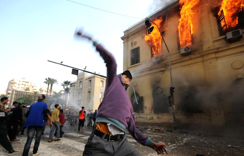 FILE - In this Dec. 17, 2011 file photo, an Egyptian protester throws a stone toward soldiers, unseen, as a building burns during clashes near Tahrir Square, in Cairo, Egypt. In an authoritative report due out Monday, March 31, 2014, a United Nations climate panel for the first time is connecting hotter global temperatures to hotter global tempers. Top scientists are saying that climate change will complicate and worsen existing global security problems, such as civil wars, strife between nations and refugees. (AP Photo/Ahmad Hammad, File)