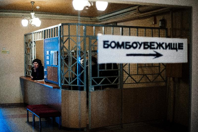 "An employee of the Donetsk State Academic Opera and Ballet Theatre is reflected in mirror next to a sign reading ""bomb shelter"" in Donetsk on March 25, 2015 (AFP Photo/Dimitar Dilkoff)"