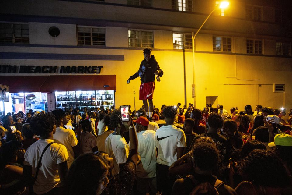 A man stands on a car as crowds defiantly gather in the street while a speaker blasts music an hour past curfew in Miami Beach, Fla., on Sunday, March 21, 2021. An 8 p.m. curfew has been extended in Miami Beach after law enforcement worked to contain unruly crowds of spring break tourists.  (Daniel A. Varela/Miami Herald via AP)