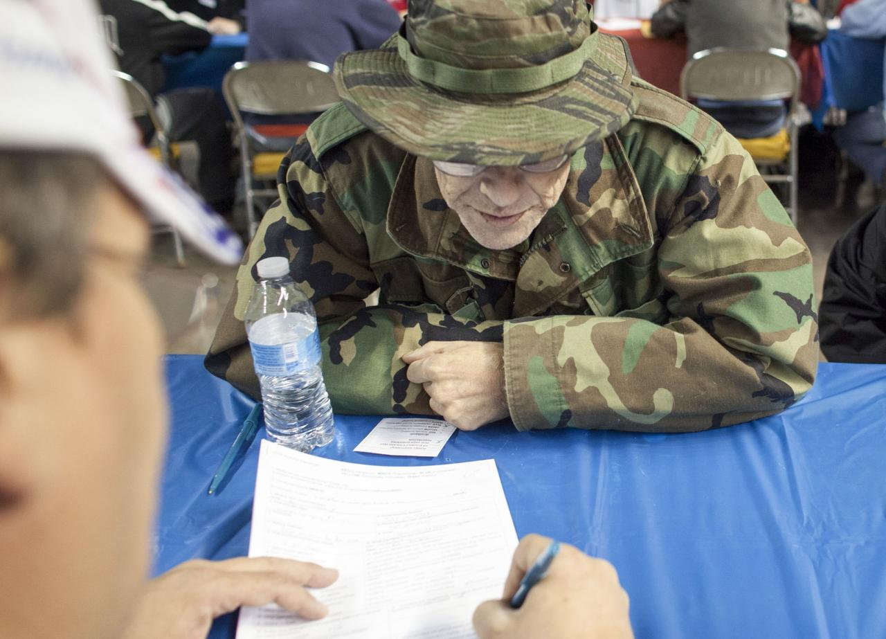 United States Army veteran James Mitten checks in with Veteran Affairs to verify his eligibility for services at the 13th annual StandDown in Phoenix, Arizona February 14, 2014. More than 1500 homeless veterans in the area were expected to receive help from 70 providers with health care, clothing and legal services. REUTERS/Samantha Sais (UNITED STATES - Tags: POLITICS SOCIETY POVERTY)