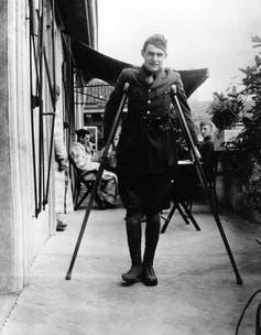 A man in army uniform stands on crutches.