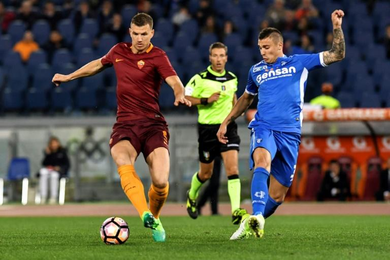 Roma's Edin Dzeko (L) vies with Empoli's Vincent Laurini during their match on April 1, 2017 at Olympic stadium in Rome