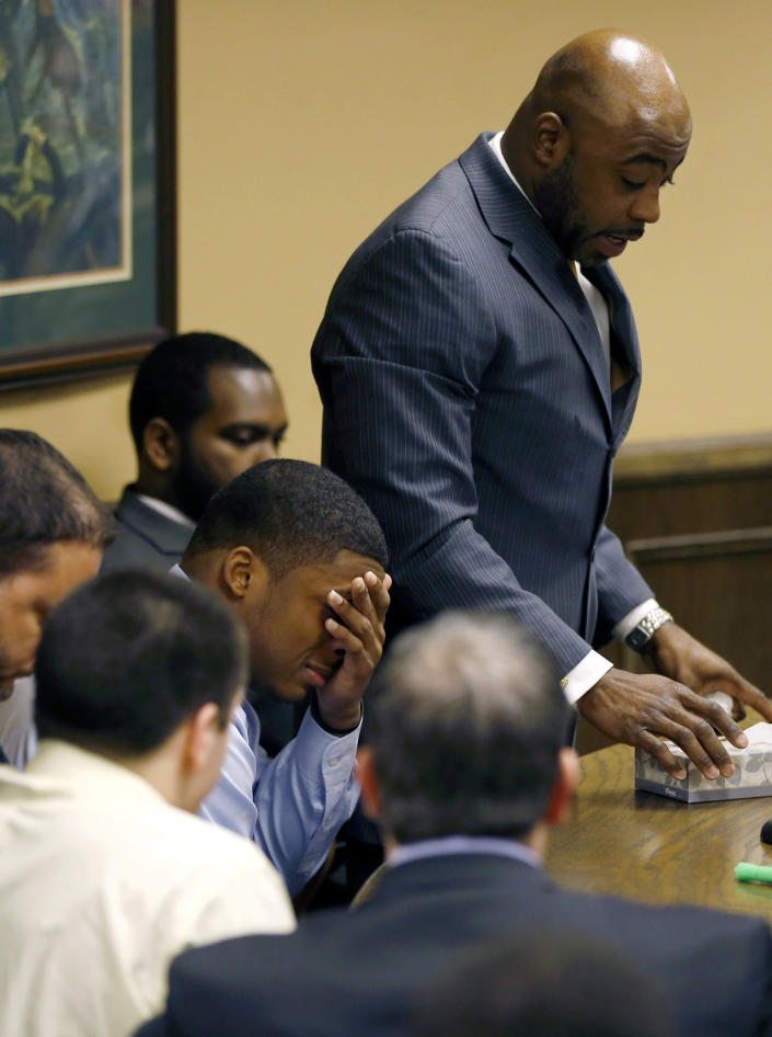 Ma'lik Richmond covers his eyes and cries as his attorney Walter Madison, standing, asks the court for leniency after Richmond and co-defendant Trent Mays, lower left, were found delinquent on rape and other charges after their trial in juvenile court in Steubenville, Ohio, Sunday, March 17, 2013. Mays and Richmond were accused of raping a 16-year-old West Virginia girl in August 2012. (AP Photo/Keith Srakocic, Pool)