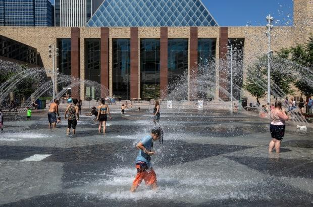 People cool off in Edmonton's city hall pool as temperatures hit 37 C in the provincial capital last month. Temperatures as high as 33 C are expected across much of Alberta this week, according to Environment and Climate Change Canada.  (Jason Franson/The Canadian Press - image credit)