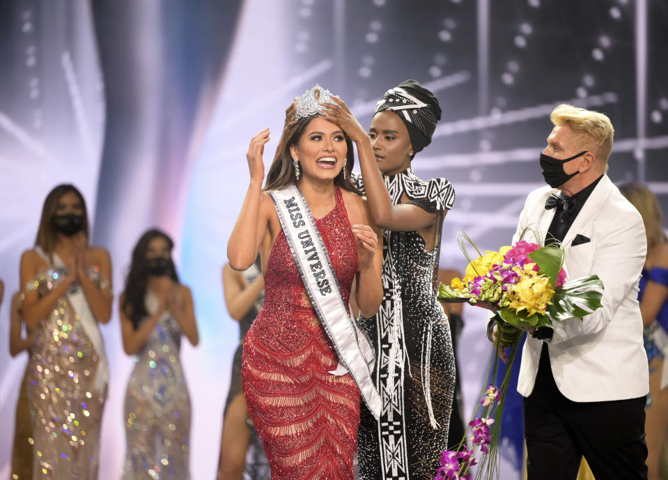 This image released by Miss Universe Organization shows Miss Universe Mexico 2020 Andrea Meza being crowned Miss Universe by Miss Universe 2019 Zozibini Tunzi at the 69th Miss Universe Competition at the Seminole Hard Rock Hotel & Casino in Hollywood, Fla. on Sunday, May 16, 2021. (Benjamin Askinas/Miss Universe via AP)