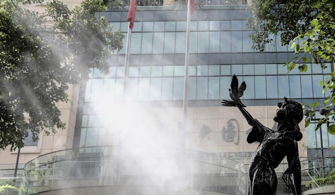 A statue outside the Hong Kong Central Library is disinfected ahead of the library's reopening. Photo: Nora Tam