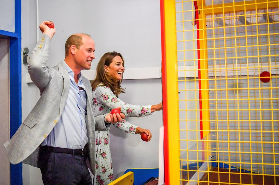 BARRY, WALES - AUGUST 05:  Prince William, Duke of Cambridge and Catherine, Duchess of Cambridge throw balls to knock down figures on an arcade game at Island Leisure Amusement Arcade, where Gavin and Stacey was filmed, during their visit to Barry Island, South Wales, to speak to local business owners about the impact of COVID-19 on the tourism sector on August 5, 2020 in Barry, Wales. (Photo by Ben Birchall - WPA Pool/Getty Images)
