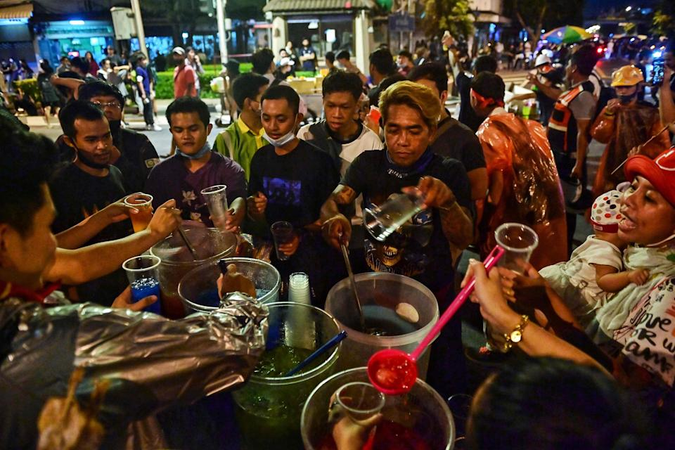 Pro-democracy protesters pause to grab drinks from a street vendor in Bangkok on Wednesday  (AFP via Getty Images)