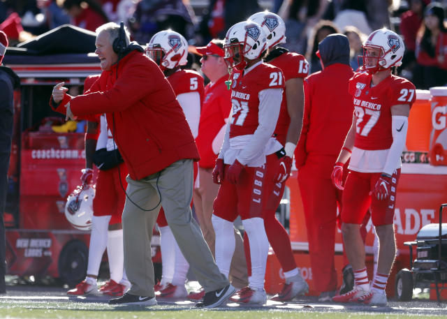 New Mexico coach Bob Davie, left, indicates instructions to his players from the sideline during the first half of an NCAA college football game against Utah State on Saturday, Nov. 30, 2019 in Albuquerque, N.M. Davie coached his final game for the Lobos as he and the University of New Mexico mutually agreed to part ways. (AP Photo/Andres Leighton)