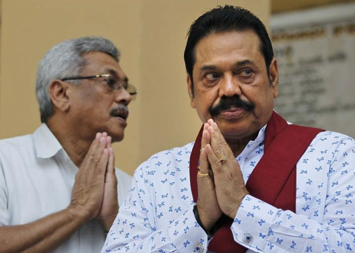 FILE- In this Feb. 8, 2016 file photo, former Sri Lankan President Mahinda Rajapaksa, right, and former Defense Secretary and his brother Gotabaya Rajapaksa, offer prayers during a function organized to sign a petition against UN recommended investigation into alleged war atrocities in Colombo, Sri Lanka. Nandasena Gotabaya Rajapaksa, who was a livewire in Sri Lanka's military campaign to end a long civil war but faces allegations of human rights violations, has been nominated as the opposition's candidate for the presidential election scheduled for later this year. (AP Photo/Eranga Jayawardena, File)