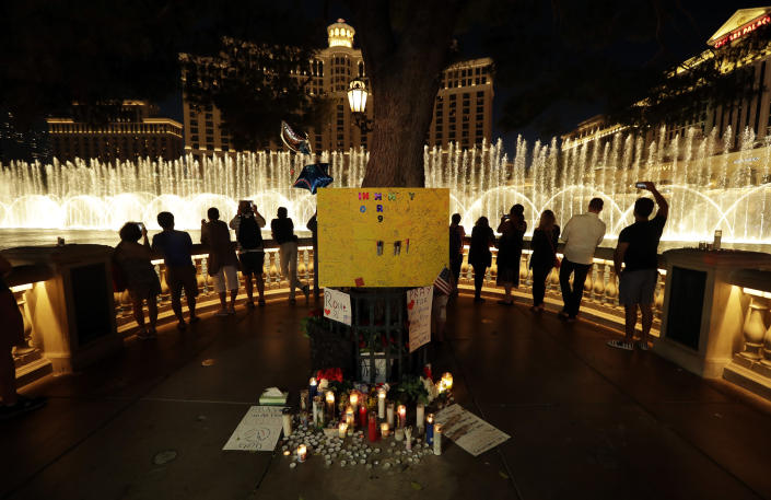 <p>People take photos of the fountain at the Bellagio hotel in front of a memorial for victims of the mass shooting in Las Vegas, Tuesday, Oct. 3, 2017. (Photo: Gregory Bull/AP) </p>