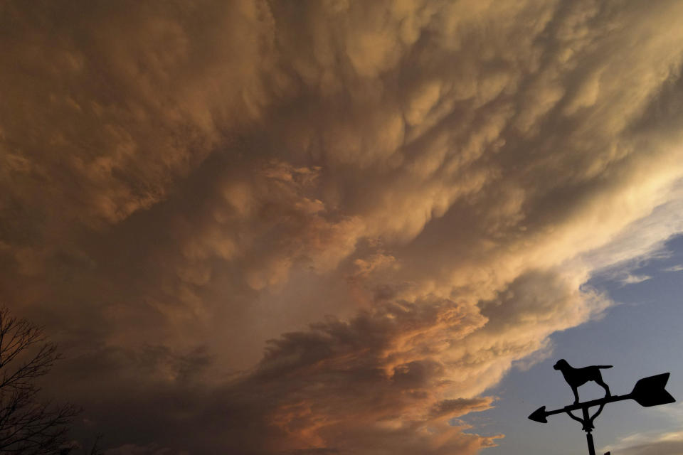 A weather vane sits on top of a garage as clouds are illuminated by the setting sun following a storm, Friday, July 24, 2020, in Lutherville-Timonium, Md. (AP Photo/Julio Cortez)