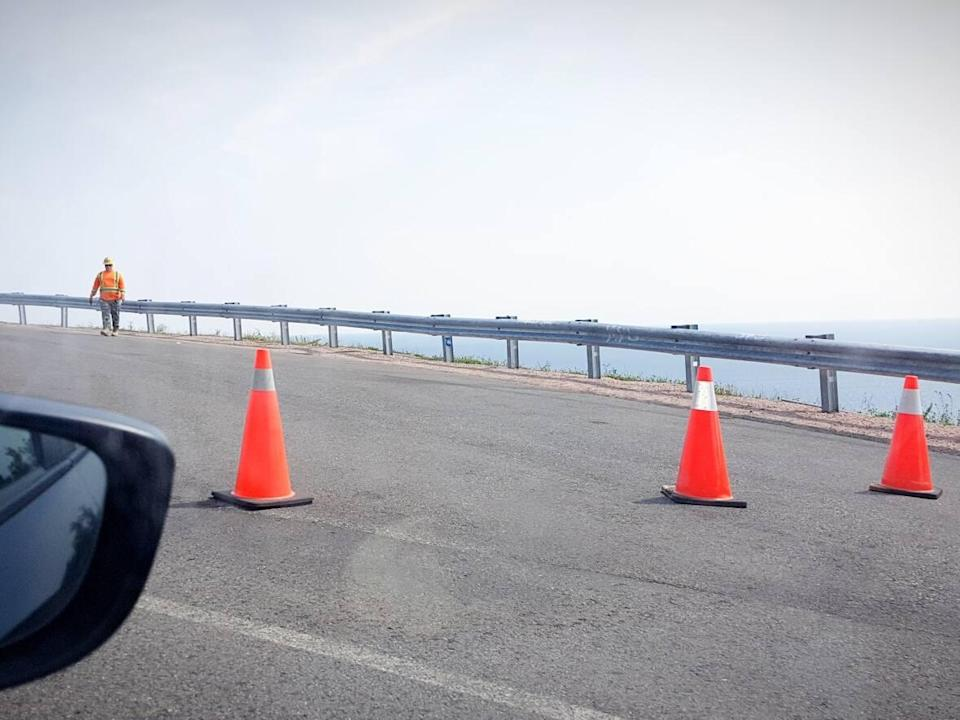 A Nova Scotia official is seen in this file photo from August 2021 after traffic cones were placed on a new look-off on Cape Smokey, where cracks have appeared in the Cabot Trail pavement. (Tom Ayers/CBC - image credit)