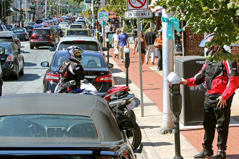 A motorcyclist pays a parking meter as traffic streams by on Main Street in Newark, Del.
