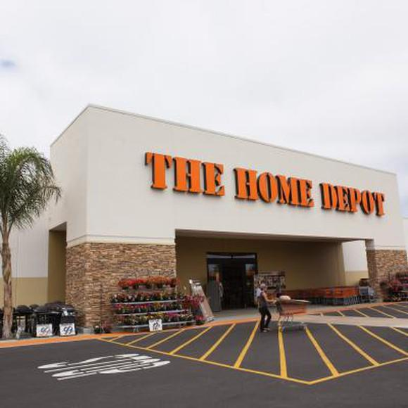 The front door of a Home Depot viewed from the parking lot. A customer is pushing a cart through the front door.