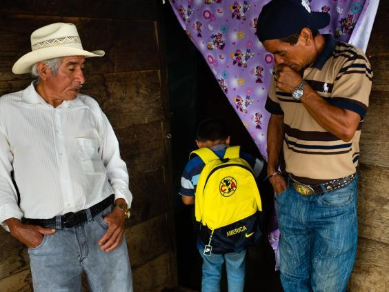 Carrillo's son shows his father's friends the Club America backpack he will use when he travels through Mexico towards the US (Sarah L Voisin/Washington Post)