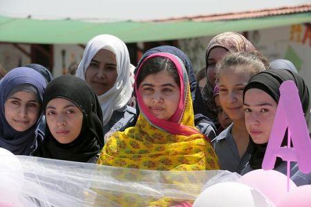 Nobel Peace Prize laureate Malala Yousafzai poses with girls for a picture at a school for Syrian refugee girls, built by the NGO Kayany Foundation, in Lebanon's Bekaa Valley