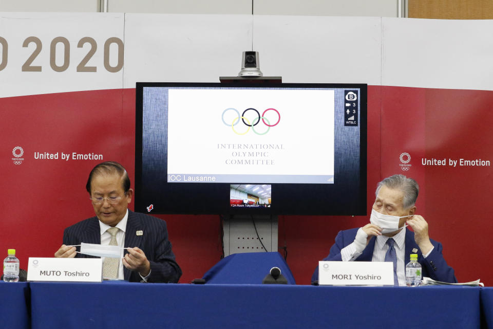 CEO of Tokyo 2020 Toshiro Muto and President of Tokyo 2020 Yoshiro Mori wear face masks as they leave a joint press conference between the International Olympic Committee (IOC) and Tokyo Organizing Committee of the Olympic and Paralympic Games (Tokyo 2020) Friday, Sept. 25, 2020, in Tokyo. (Rodrigo Reyes Marin/Pool Photo via AP)