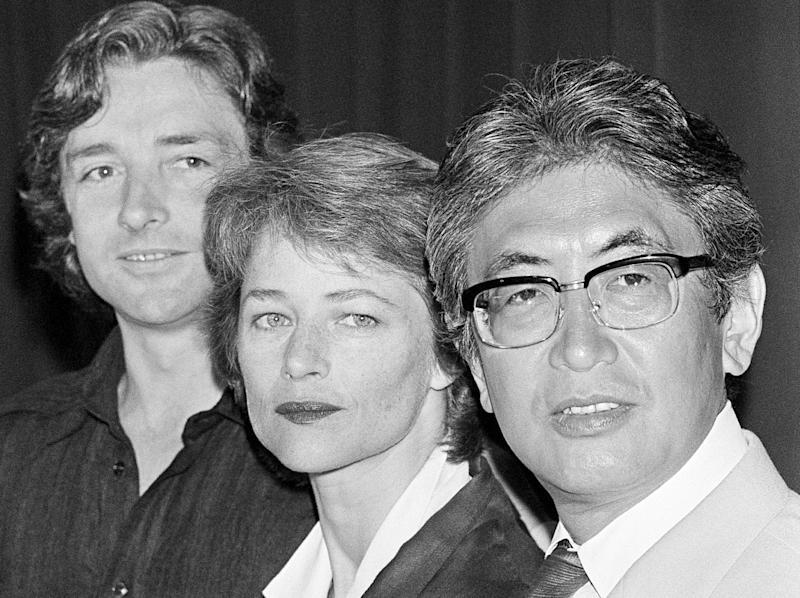 """FILE - In this May 13, 1986 file photo, Japanese film director Nagisa Oshima, right, who's film """"Max My Love"""" is in competition during the 39th Film Festival in Cannes, France, poses with British actress Charlotte Rampling, center, and British actor Anthony Higgins, left, at Cannes, France. Oshima, a Japanese director known for internationally acclaimed films """"Empire of Passion"""" and """"In the Realm of the Senses"""" has died of pneumonia. He was 80. His office says Oshima died Tuesday afternoon, Jan. 15, 2013, at a hospital near Tokyo.(AP Photo/File)"""