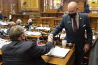Georgia State Sen. Mike Dugan (R-Carrollton) shakes hands with Rules Committee Chairman Sen. Jeff Mullis (R-Chickamauga) after the passage of Senate Bill 241, which changes Georgia's voting laws, Monday, March 8, 2021, at the State Capitol in Atlanta. Dugan presented the bill. (AP Photo/Ben Gray)