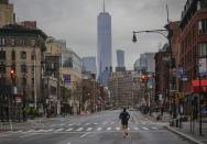 """A lone jogger run on a partially empty 7th Avenue, resulting from citywide restrictions calling for people to stay indoors and maintain social distancing in an effort to curb the spread of COVID-19, Saturday March 28, 2020, in New York. President Donald Trump says he's considering a quarantine affecting residents of the state and neighboring New Jersey and Connecticut amid the coronavirus outbreak, but New York Gov. Andrew Cuomo said that roping off states would amount to """"a federal declaration of war."""" (AP Photo/Bebeto Matthews)"""