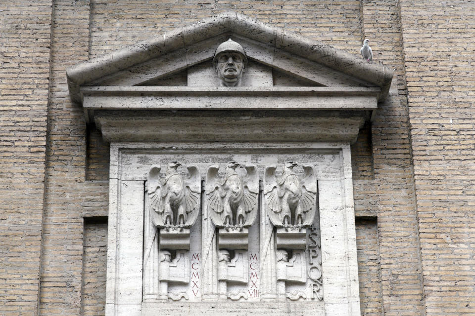 FILE - In this Friday, May 3, 2019. file photo, fasces, the original symbol of Fascism adapted from ancient Rome, showing a bundle of rods tied together around an axe, are seen carved with eagles on the facade of the Madonna dei Monti church, above a plaque commemorating the fallen soldiers of WWI, in downtown Rome. An extreme-right political party's violent exploitation of anger over government anti-pandemic restrictions is forcing Italy to wrestle with its fascist legacy and fueling fears that there could be a replay of last week's mobs trying to force their way toward Parliament. (AP Photo/Andrew Medichini, File)