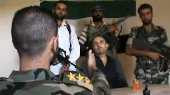 This image made from amateur video released by the Shaam News Network purports to show Syrian Pilot Colonel Rafik Mohammed Suleiman being interrogated by a rebel officer after his Soviet-made MiG warplane was apparently hit by ground fire over Deir el-Zour province, an area near the Iraqi border, Syria, Monday, Aug. 13, 2012. If the rebel claim of the downing proves true, it could mark a significant jump in their ability to combat widening air attacks from President Bashar Assad's forces. (AP Photo/Shaam News Network) THE ASSOCIATED PRESS IS UNABLE TO INDEPENDENTLY VERIFY THE AUTHENTICITY, CONTENT, LOCATION OR DATE OF THIS HANDOUT PHOTO
